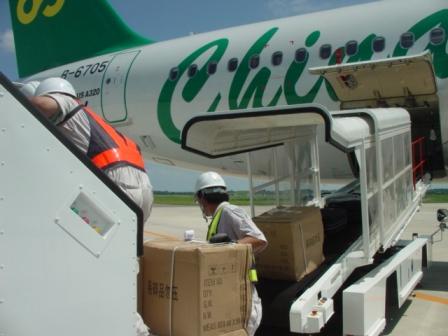春秋航空A320に貨物を搬入する様子。ベルトローダ車を使います。