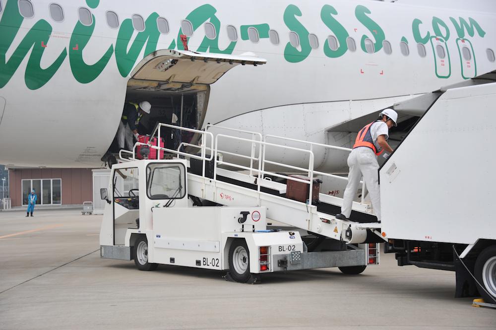 春秋航空のA320から手荷物を降ろす様子。